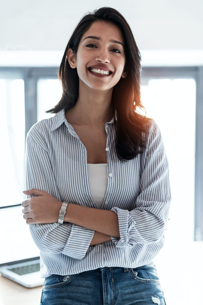 Elegant young business woman looking at camera while standing in the office.