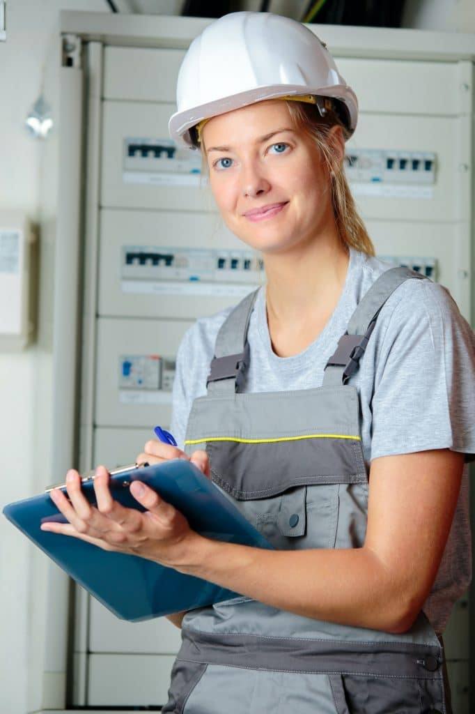 Portrait of female electrician with clipboard