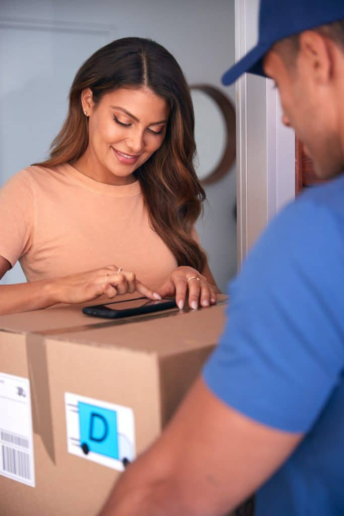 Woman Signing For Package Delivered By Courier On Mobile Phone