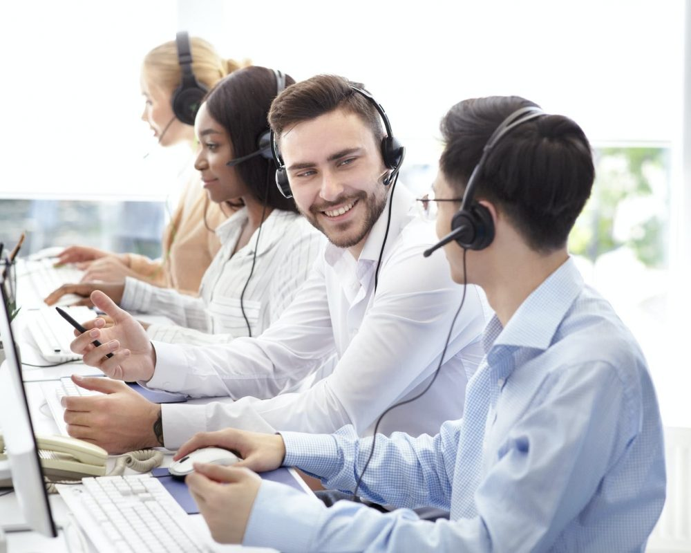 Happy male technical support operators having friendly chat at call centre