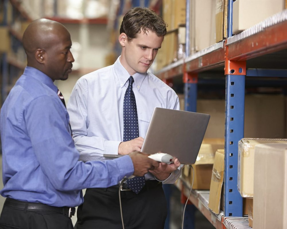 Two Businessmen With Laptop In Warehouse